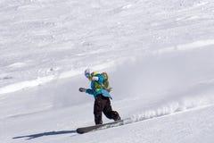 Snowboarder que va abajo de la cuesta en la estación de esquí Imagen de archivo
