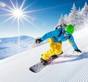 Snowboarder que vai para baixo nas montanhas altas Foto de Stock Royalty Free