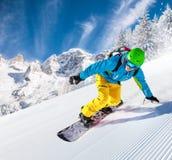 Snowboarder que vai para baixo nas montanhas altas Imagens de Stock