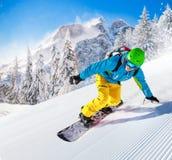 Snowboarder que vai para baixo nas montanhas altas Fotografia de Stock Royalty Free