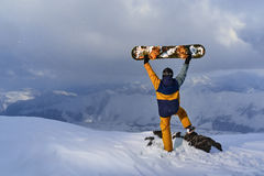 Snowboarder raised  board above his head standing on a cliff Royalty Free Stock Photos