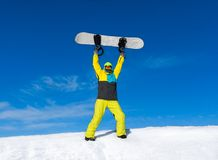 Snowboarder raised hands arms up hold snowboard on Stock Photos