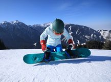 Snowboarder ready for snowboarding. One young woman snowboarder ready for snowboarding on winter mountain top Stock Image