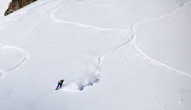 Snowboarder remoto che guida polvere fresca Fotografia Stock