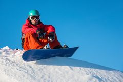 Snowboarder resting in the mountains royalty free stock photography
