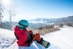 Snowboarder resting in the mountains. Rearview shot of a relaxed man snowboarder lying on the snowy slope enjoying stunning mountains view resting after riding Stock Image