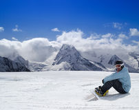 Snowboarder resting on the ski slope Stock Photography