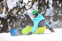 Snowboarder resting on a slope Royalty Free Stock Image