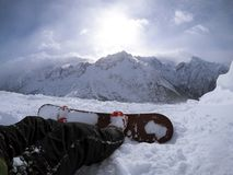 Snowboarder resting on the slope - winter sports scene. Beautiful mountain view.  Stock Images