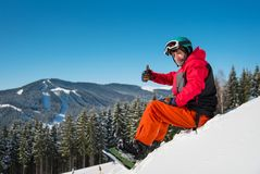 Snowboarder resting on top of the mountain. Shot of a happy snowboarder sitting, relaxing on top of the mountain, showing thumbs up to the camera copyspace Royalty Free Stock Photography