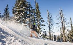 Snowboarder ride on powder snow to the mountains. Winter sports freeride.  Stock Photo