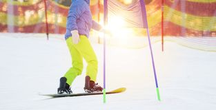 Snowboarder rides her snowboard downhill stock photo