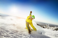 Snowboarder rides on the slope  snow mountains background Stock Image