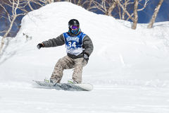 Snowboarder rides steep mountains. Kamchatka, Far East, Russia Royalty Free Stock Image