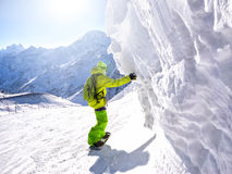Snowboarder. Riding along ice wall in ski resort at mountain background Royalty Free Stock Photo