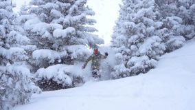 Snowboarder riding deep powder snow in Slow Motion. Snowboarder carving in fresh snow. Extreme free ride snowboarder riding fresh stock footage