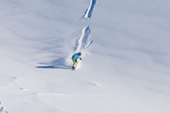 Snowboarder riding down on fresh backcountry snow. Snowboarder freeriding down on fresh backcountry snow Stock Photo