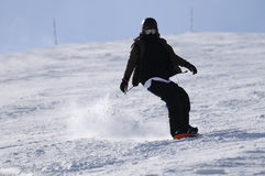 Snowboarder riding down the slope Stock Images