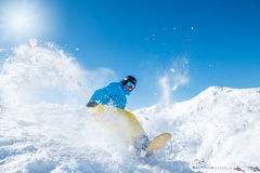 Snowboarder riding down the slope. Snowboarder in wintersport outfit riding down the slope at a ski resort Royalty Free Stock Photo