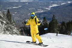 Snowboarder riding down the slopes wearing yellow mono suit on sunny day with fresh snow.