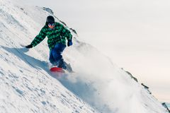 Snowboarder is riding down from snow hill Stock Images