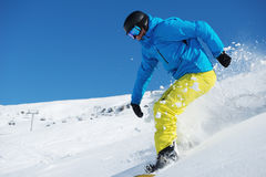Snowboarder riding down. The snowy hill in the ski resort Stock Photography