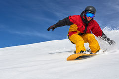 Snowboarder riding fast on dry snow freeride slope. Royalty Free Stock Photos