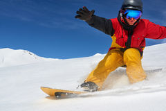 Snowboarder riding fast on dry snow freeride slope. Royalty Free Stock Photography
