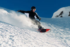Snowboarder is riding from snow hill Royalty Free Stock Images