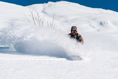 Snowboarder is riding from snow hill Stock Photography
