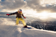 Snowboarder is riding on the sunset Royalty Free Stock Photo