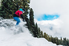 Snowboarder is riding very high and freeriding from hill in the mountain forest. Snowboarder with special equipment is riding very fast and freeriding from hill Royalty Free Stock Photo
