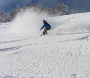 Snowboarder ripping into the fresh snow. A bluebird day at Hanazono Japan Stock Photography