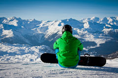Snowboarder seated looking the mountains Royalty Free Stock Image