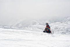 Snowboarder siedzi na szczyciefal tg0 0n w tym stadium góry Obraz Royalty Free