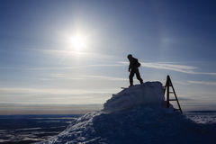 Snowboarder silhouette in sunlight on mountain top ready for descent Royalty Free Stock Photos