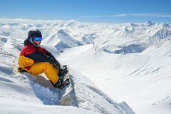 Snowboarder sits high in mountains on the edge of slope Royalty Free Stock Photo