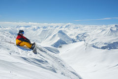 Snowboarder sits high in mountains on the edge of slope Stock Photo