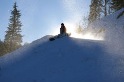 Snowboarder sitting in front of the sun. In snow royalty free stock image