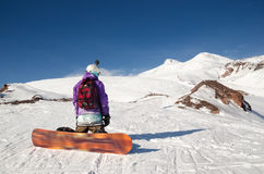 Snowboarder is sitting on mountain slopes of an extinct volcano Elbrus Royalty Free Stock Photography