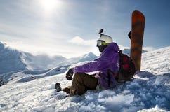 Snowboarder is sitting on mountain slopes of an extinct volcano Elbrus Stock Photos
