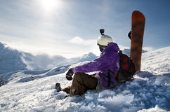 Snowboarder is sitting on mountain slopes of an extinct volcano Elbrus Stock Photo