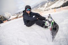 Snowboarder sitting on a ski slope before ride. Snowboarder sitting on a ski slope on hill Stock Photos