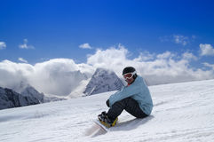 Snowboarder sitting on the snow Stock Image
