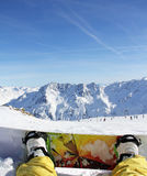 Snowboarder sitting on snow. In high mountains Stock Photo