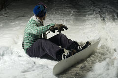 Snowboarder sitting in snow Stock Images