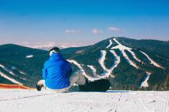 Snowboarder sitting on snow against mountains Stock Images