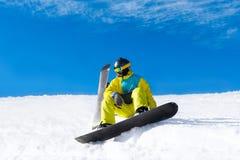 Snowboarder sitting on snow mountain slope Stock Image