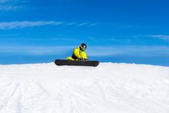 Snowboarder sitting on snow mountain slope Royalty Free Stock Photography
