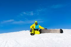 Snowboarder sitting on snow mountain slope Stock Photography